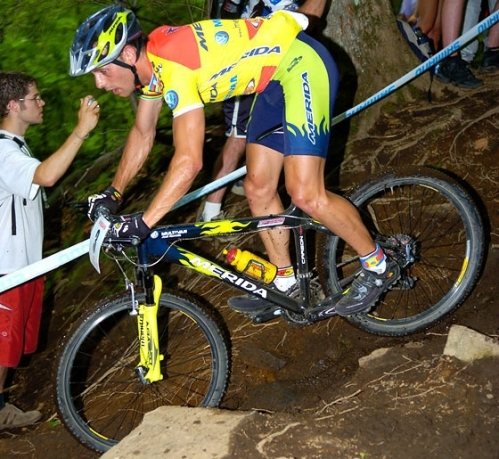 Hermida en Mont St. Anne, junio 2005, luciendo el maillot de campeón de España que consiguió por tercera vez en 2004. Hermida sigue confiando en los frenos de zapatas a pesar de la humedad. Por aquel entonces el equipo corría patrocinado por la marca de cubiertas Maxxis y el de componentes FSA. Una lianza casi tradicional en la marca. Además Hermida corría con SRAM gripshift (mandos de cambio giratorios). La horquilla es una Manitou R7 que saldría al mercado meses después para sustituir al modelo Skareb, pero esta vez en lugar de barras de 28mm con 30mm, siguiendo la tendencia oversize de los nuevos componentes de bici. Un rollo vamos.